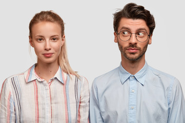 Wall Mural - Photo of attractive blonde woman with pony tail, curious unshaven guy stand shoulder to shoulder against white background, have friendly relationships. Two colleagues meet together for making project