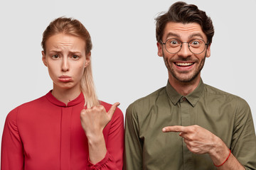 Wall Mural - Photo of discontent girlfriend has quarrel with boyfriend, wears red blouse, points with thumb at cheerful man, doesnt like something. Positive Caucasian male makes fun of beautiful girl, stand indoor
