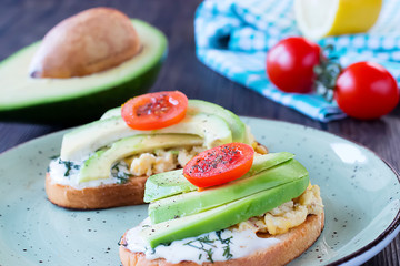 Toasts with avocado pieces, cherry tomatoes, scrambled eggs and soft cream cheese.