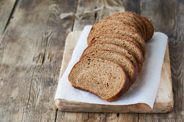 Slices of fresh rye bread on a wooden cutting board