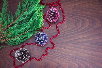 New Year's colorful cones and branches of a green Christmas tree with decor in the form of red beads
