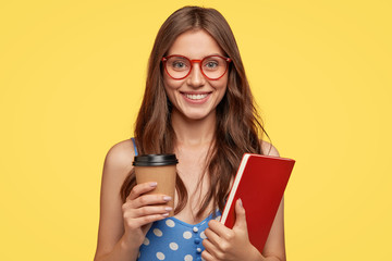 Photo of cheerful female college student carries execise book and take out coffee, smiles broadly, being in good mood after lectures, rejoices coming holidays, models against yellow studio wall