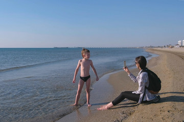 Mom takes a foto and video on mobile phone of her son little blogger walking by the sea.
