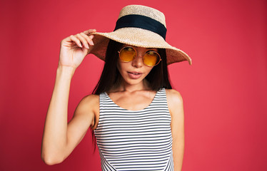 Excited and happy beautiful lovely young woman in sunglasses, dress and summer hat is have a fun while posing on pink background