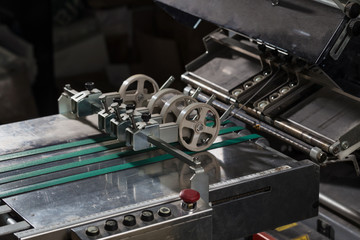Folding machine industrial. Demonstration of the workflow. Equipment for color printing.