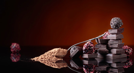 Chocolate candies, broken chocolate pieces and spoon with cocoa powder.