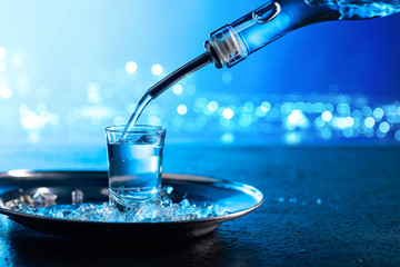 Vodka poured into a glass lit with blue backlight.