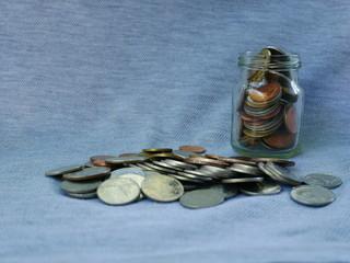 coins spilling out of glass jar on black background