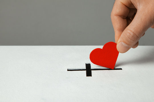 Donation of your heart as symbol of love for the religion of Christianity. Box for donations with slot in the form of Christian christe. Man puts hand donations. Copy space for text