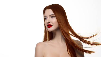 Close-up portrait of a fiery redhead sexy woman with red lipstick on her lips. Pure pale white skin. Beauty care and spa treatments. Long luxurious hair develops on a white isolate background.
