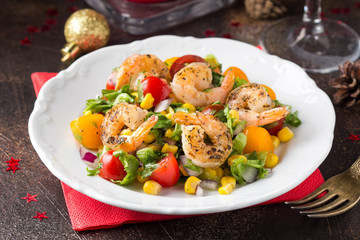 Salad with corn, fried shrimp, cherry tomatoes, red onions and lettuce on white plate. Appetizer for Christmas party