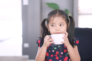 Asian child cute or kid girl delicious hot cocoa or chocolate and milkshake drink with holding white cup and funny or happy for breakfast in morning at home or cafe restaurant and coffee shop