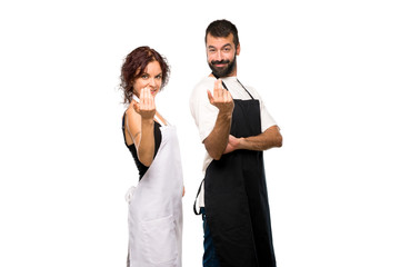 Couple of cooks presenting and inviting to come with hand on isolated white background