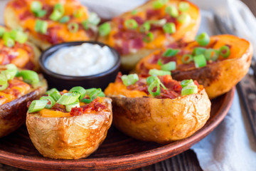 Baked loaded potato skins with cheddar cheese and bacon, garnished with scallions and sour cream horizontal