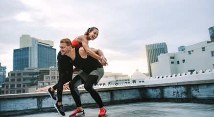 Fitness couple having fun while training on rooftop