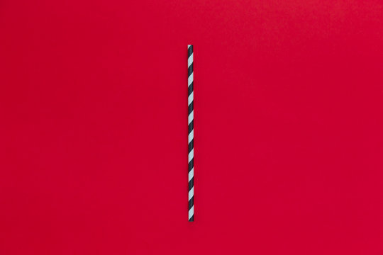 Black striped eco paper straw on red background.