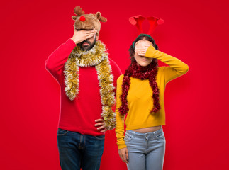 Couple dressed up for the christmas holidays covering eyes by hands. Do not want to see something on isolated red background