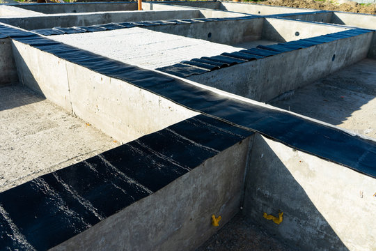 Workers carry out waterproofing of the Foundation for the construction of a wooden house.