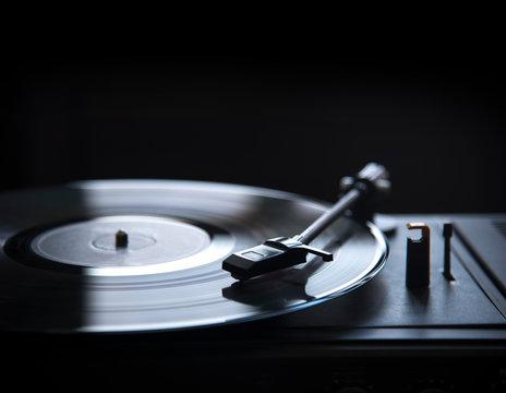 Retro gramophone vinyl player over black background with copyspace.