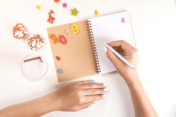 To do list for New year 2019 and Christmas. Woman hand holding pen on opened notebook. Goals plans dreams make wish list for Christmas. Winter holidays. Flat lay, top view, copy space, mock up