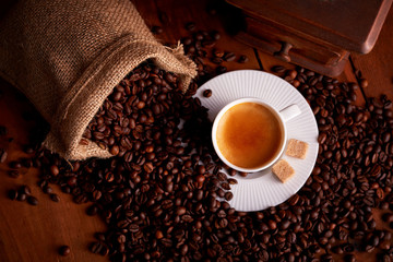 Top view of cup of espresso with coffee beans and old ginger on wooden table