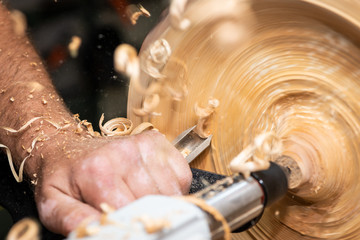 turnery of a wooden bowl with spiral sawdust shavings with hand and chisel