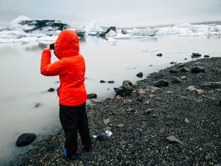 Girl taking photos to icebergs.