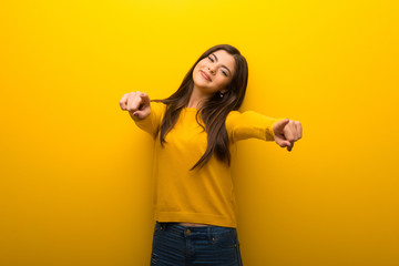 Teenager girl on vibrant yellow background points finger at you while smiling Wall mural