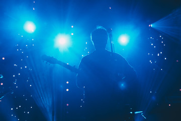 Rock band front man silhouette on a stage with guitar singing to microphone in colorful backlights