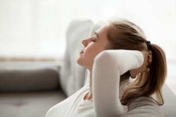 Close up of calm young female relax on cozy couch with eyes closed, peaceful girl lying on sofa hands over head having rest at home, dreamy woman stretching enjoying weekend morning in apartment Fotomurais