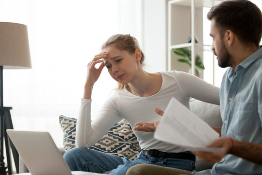 Millennial couple have fight over documents at home, man and woman sit on couch upset about bad news in letter, frustrated wife cry reading negative notice from bank, spouses dispute over bills