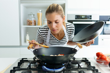 Healthy young woman cooking and smelling food in frying pan in the kitchen at home.