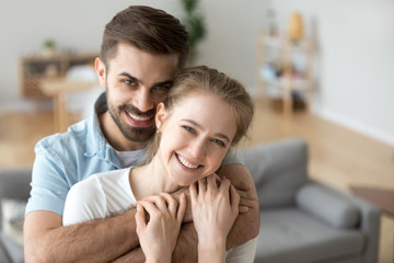 Portrait of happy millennial couple hug looking at camera, smiling husband hold in arms beloved young wife posing in living room, headshot of excited first time buyers make family picture in new home