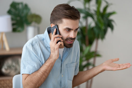 Angry man talk on smartphone arguing or solving problem, irritated male have cell phone conversation manage work trouble, annoyed guy use mobile call customer service disputing or complaining