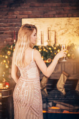 Attractive happy woman with long blonde hair holding a glass of champagne and smiling against the background of Christmas lights and decors