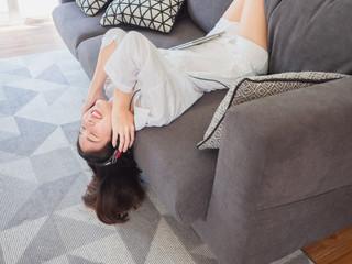 asian girl listening music in headphones on sofa