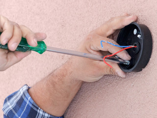 Electricians hands installing an exteriror light