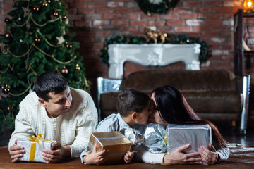family lying on the floor with gift boxes on Christmas tree background