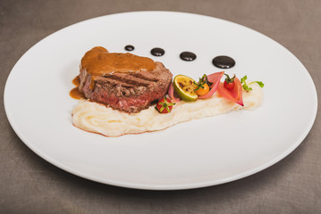 Pepper steak, served with potatoes, strawberry and cherry tomato