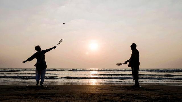 Active senior couple playing tai chi ballon ball at the beach.