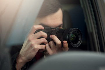 Young Male Spy Sits In The Car Taking Photos To The Camera With A Zoom Lens. Detective Agency Concept