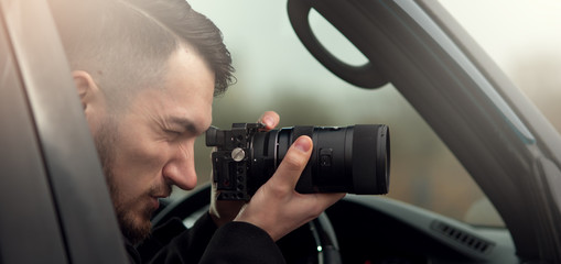 Close-up - Young Man Photorapher Sitting In The Car And Quickly Took A Photo On A Digital Camera. Concept Of Espionage And Photography