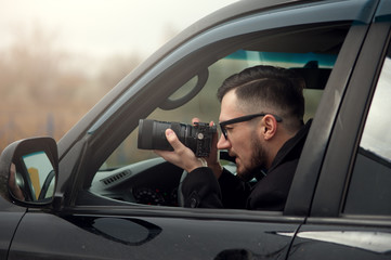 Young Male Photographer Takes A Camera With A Zoom Lens And Takes Pictures. Concept Of Espionage And Photography