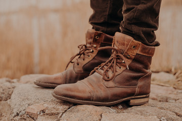 Image of man in brown old leather boots and trousers stands on stones against blurred background. Shabby shoes. Selling of shoes. Coming winter