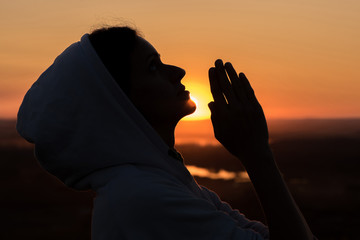 Beautiful woman praying at sunset against the sky in summer