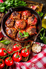 Homemade baked meatballs with tomato sauce in small frying pan on dark rusty stone table. Top view  copy space