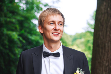 groom at wedding tuxedo smiling and waiting for bride. Rich groom at wedding day. Elegant groom in costume and bow-tie.