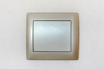 light switch with one large key button in the interior of the home on the wall