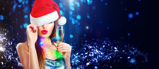 Christmas sexy woman. Beauty model girl in Santa's hat with glass of champagne in her hand celebrating on blinking holiday winter wide background