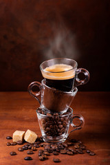 glass cups, in sequence vertically, with coffee beans, ground, and steaming drink. still life